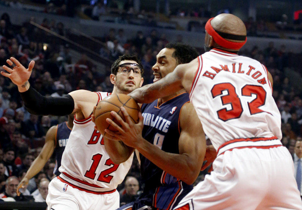 Chicago Bulls guard Richard Hamilton (32) fouls Charlotte Bobcats guard Gerald Henderson as Bulls guard Kirk Hinrich (12) defends during the first half of an NBA basketball game, Monday, Jan. 28, 2013, in Chicago. (AP Photo/Charles Rex Arbogast)