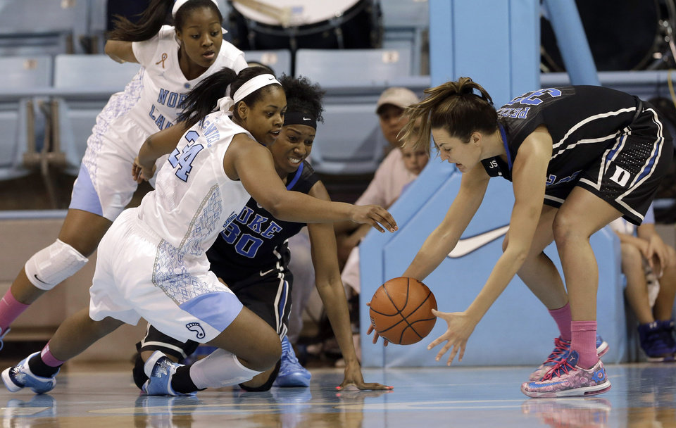 Photo - Duke's Haley Peters, right, and Amber Henson (30) reach for a loose ball against North Carolina's Xylina McDaniel (34) and Stephanie Mavunga during the first half of an NCAA college basketball game in Chapel Hill, N.C., Sunday, March 2, 2014. (AP Photo/Gerry Broome)