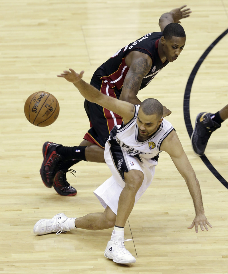 Photo - San Antonio Spurs' Tony Parker (9) loses the ball as Miami Heat's Mario Chalmers defends during the second half at Game 4 of the NBA Finals basketball series, Thursday, June 13, 2013, in San Antonio. (AP Photo/David J. Phillip)