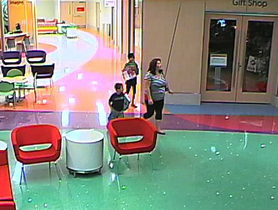 Photo - In this hospital surveillance photo released by the Phoenix Police Department on Dec. 3, 2012, a woman is seen with her 11-year-old daughter, a leukemia patient who had her arm amputated and a heart catheter inserted due to an infection. Authorities say the woman inexplicably took the girl from the hospital last week. Police say that if the catheter is left in too long it could lead to a deadly infection. The family's identity is being withheld but they are calling the girl Emily. (AP Photo/Phoenix Police Department)