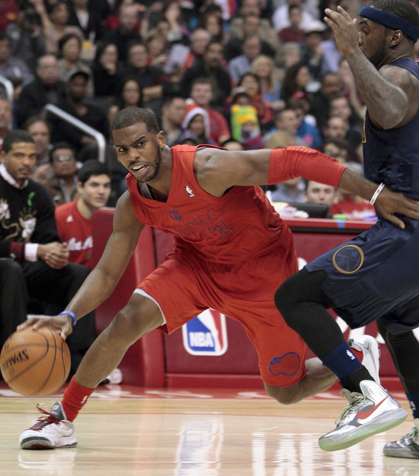 Photo - Los Angeles Clippers guard Chris Paul (3) drives to the basket as Denver Nuggets guard Ty Lawson defends during the first half of their NBA basketball game, Tuesday, Dec. 25, 2012, in Los Angeles. (AP Photo/Jason Redmond)