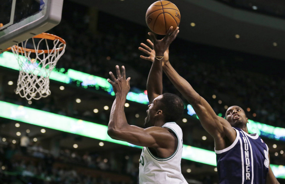 Photo - Oklahoma City Thunder forward Serge Ibaka, right, reaches as he tries to block a shot by Boston Celtics forward Jeff Green during the first quarter of an NBA basketball game in Boston, Friday, Jan. 24, 2014. (AP Photo/Charles Krupa)