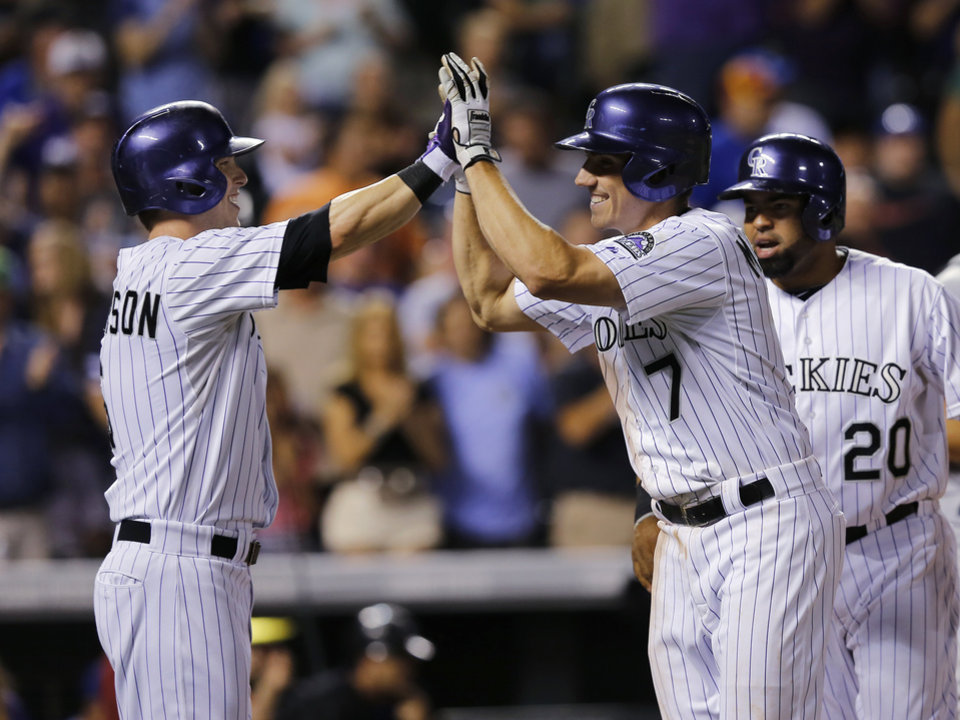 Photo - Colorado Rockies' Matt McBride (7) is congratulated at the plate by teammates Corey Dickerson, left, and Wilin Rosario after hitting a grand slam off Kansas City Royals starting pitcher Danny Duffy during the sixth inning of a baseball game Wednesday, Aug. 20, 2014, in Denver. (AP Photo/Jack Dempsey)