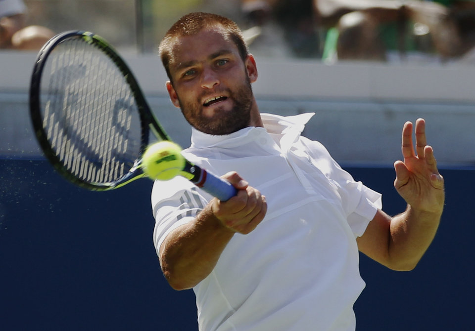 Mikhail Youzhny, of Russia, returns a shot against Nick Kyrgios, of Australia, during the opening round of the 2014 U.S. Open tennis tournament, Monday, Aug. 25, 2014, in New York. (AP Photo/Frank Franklin II)