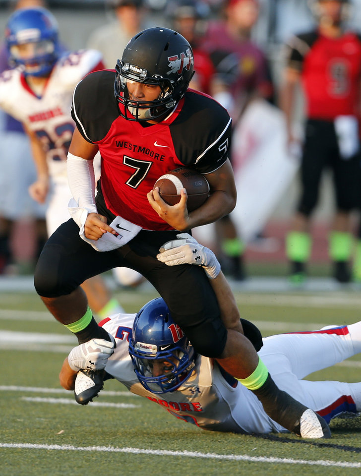 Photo - Moore's Evan Sprayberry stops Bryson Lee (7) as Westmoore plays Moore High School on Friday, Sept. 6, 2013 in Moore, Okla.  Photo by Steve Sisney, The Oklahoman