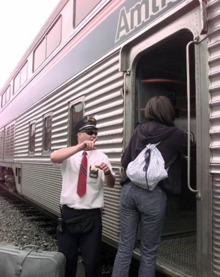Photo - Mark  Line, conductor on Amtrak's Heartland Flyer train, gives boarding instructions Wednesday, June 14, 2000, during a stop in Norman, Okla. on the first anniversary of the restoration of passenger  rail service in  Oklahoma. (AP Photo/Jerry Laizure)