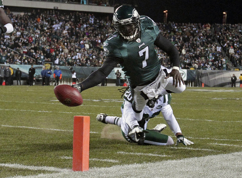 Photo - FILE - In a Dec. 18, 2011 file photo, Philadelphia Eagles quarterback Michael Vick (7) scores a touchdown in the first half of an NFL football game, in Philadelphia. The New York Jets signed quarterback Michael Vick and released Mark Sanchez on Friday, March 21, 2014. Vick was a free agent after spending the last five seasons with the Phialdelphia Eagles. (AP Photo/Matt Slocum, File)