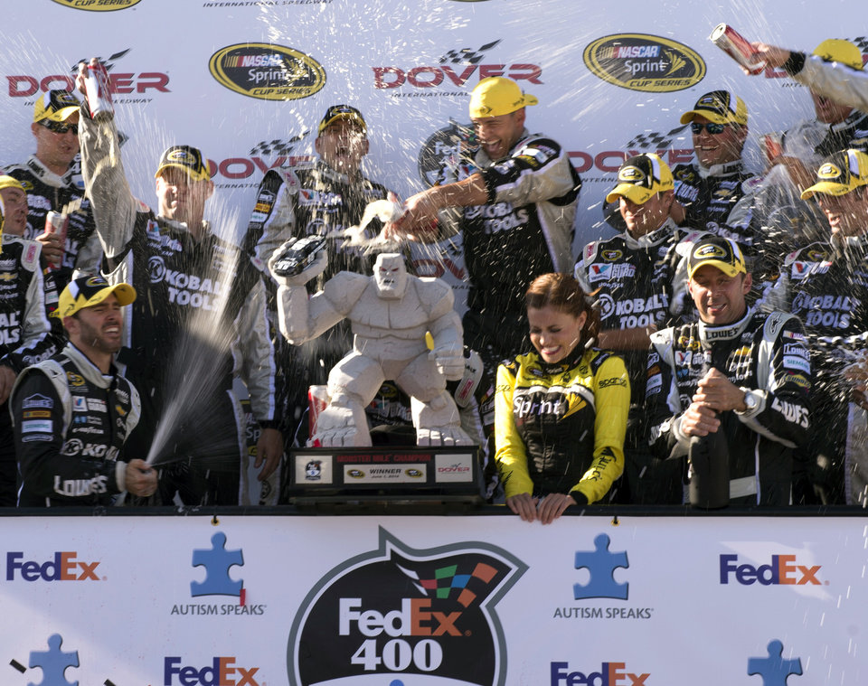 Photo - Jimmie Johnson, left, celebrates winning the NASCAR Sprint Cup series auto race at Dover International Speedway, Sunday, June 1, 2014, in Dover, Del. (AP Photo/Molly Riley)