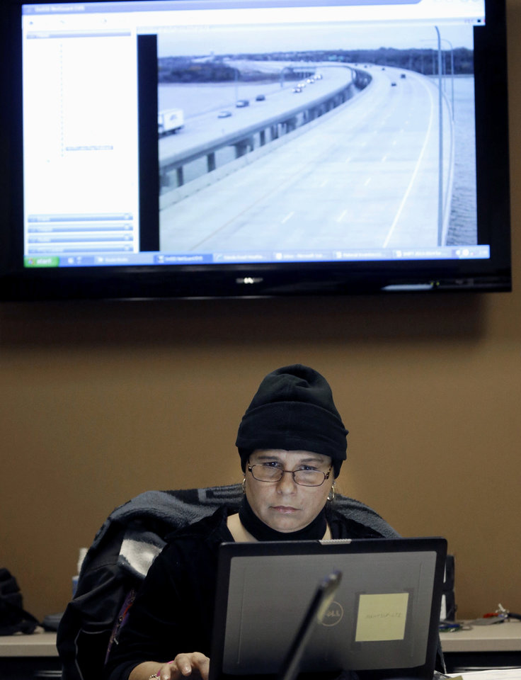 Sherry Youngblood monitors road and bridge conditions in the North Texas Tollway Authority command room in preparation for icy roads and winter weather in Plano, Texas, Thursday, Dec. 5, 2013. North Texas is preparing for an ice storm that is to arrive Thursday evening. (AP Photo/LM Otero)