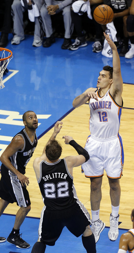 Photo - Oklahoma City's Steven Adams (12) shoots over San Antonio's Tony Parker (9) and Tiago Splitter (22) during Game 2 of the Western Conference semifinals in the NBA playoffs between the Oklahoma City Thunder and the Los Angeles Clippers at Chesapeake Energy Arena in Oklahoma City, Monday, May 7, 2014. Photo by Bryan Terry, The Oklahoman