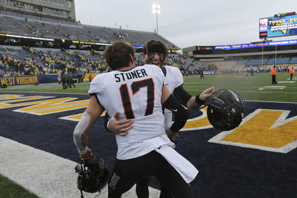 Photo - Oklahoma State quarterback Dru Brown celebrates with Dillon Stoner after an NCAA college football game against West Virginia in Morgantown, W.Va., on Saturday, Nov. 23, 2019. [AP Photo/Chris Jackson]
