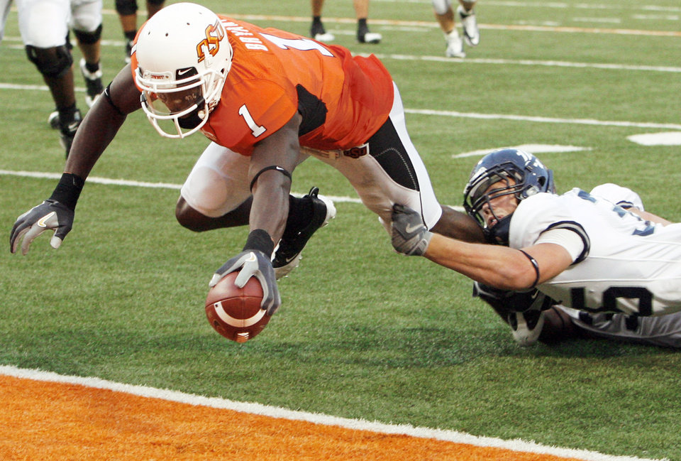 Photo - OSU's Dez Bryant, left, extends the ball for a touchdown as Rice's Travis Bradshaw tries to bring him down at the goal line. Bryant had five catches for 59 yards on the day. Photo by Nate Billings, The Oklahoman