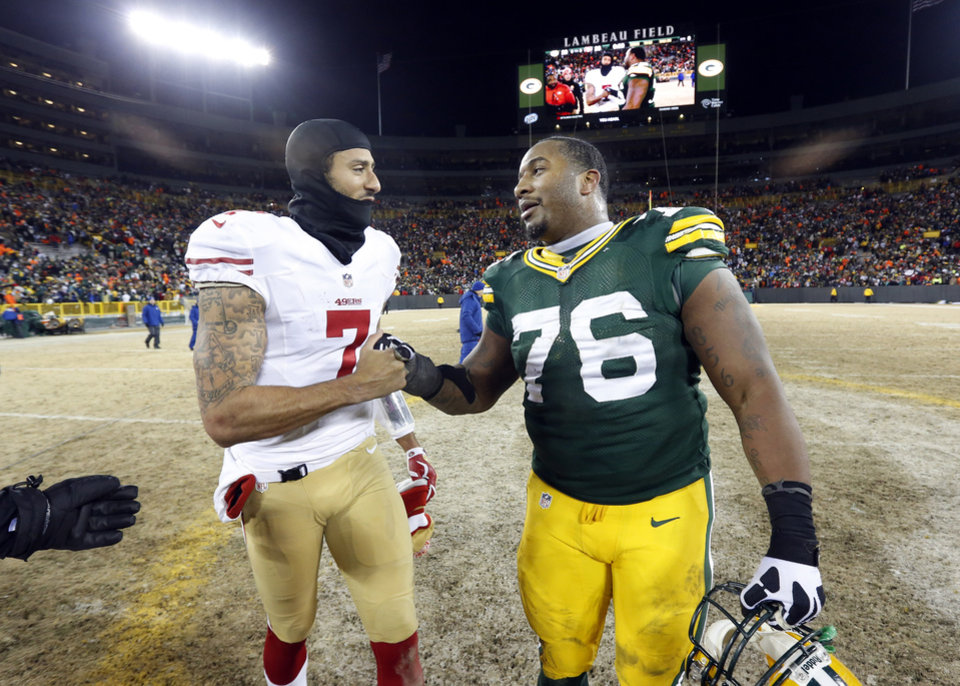 Photo - San Francisco 49ers quarterback Colin Kaepernick (7) talks to Green Bay Packers defensive end Mike Daniels (76) after an NFL wild-card playoff football game, Sunday, Jan. 5, 2014, in Green Bay, Wis. The 49ers won 23-20. (AP Photo/Mike Roemer)