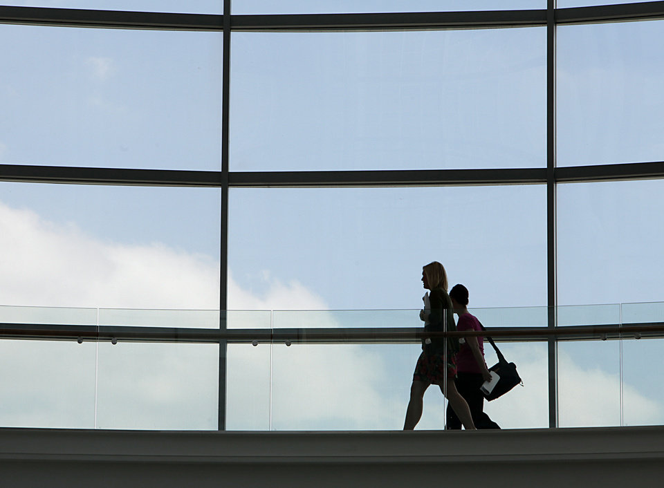Two people walk along the rotunda Monday at the Devon Energy Center, which earned gold certification for Leadership in Energy and Engineering Design. <strong>David McDaniel - The Oklahoman</strong>