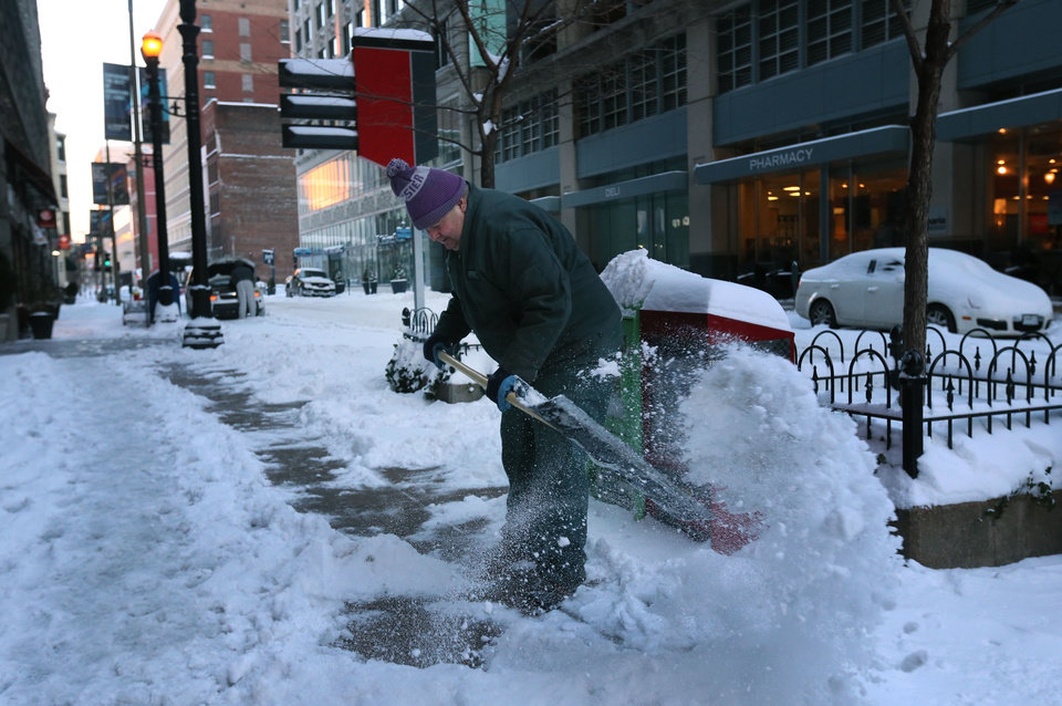 Photo - Bob Brown, a building engineer for the Frisco Building in downtown St. Louis, shovels the sidewalk along Olive Street on Monday, Jan. 6, 2014, in St. Louis. (AP Photo/St. Louis Post-Dispatch, David Carson) EDWARDSVILLE INTELLIGENCER OUT; THE ALTON TELEGRAPH OUT.