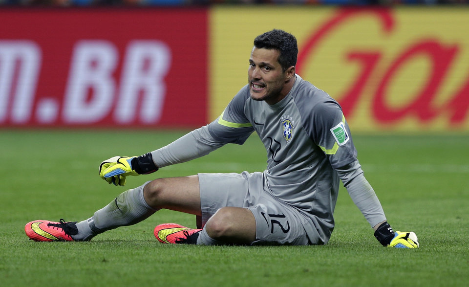 Photo - Brazil's goalkeeper Julio Cesar sits on the pitch during the World Cup semifinal soccer match between Brazil and Germany at the Mineirao Stadium in Belo Horizonte, Brazil, Tuesday, July 8, 2014. (AP Photo/Matthias Schrader)