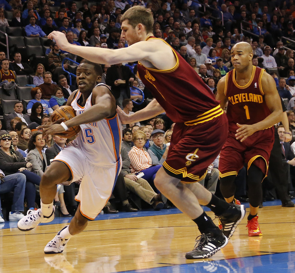 Photo - Oklahoma City's Reggie Jackson (15) drives past Cleveland's Tyler Zeller (40) during the NBA basketball game between the Oklahoma City Thunder and the Cleveland Cavaliers at the Chesapeake Energy Arena in Oklahoma City, Okla. on Wednesday, Feb. 26, 2014.  Photo by Chris Landsberger, The Oklahoman