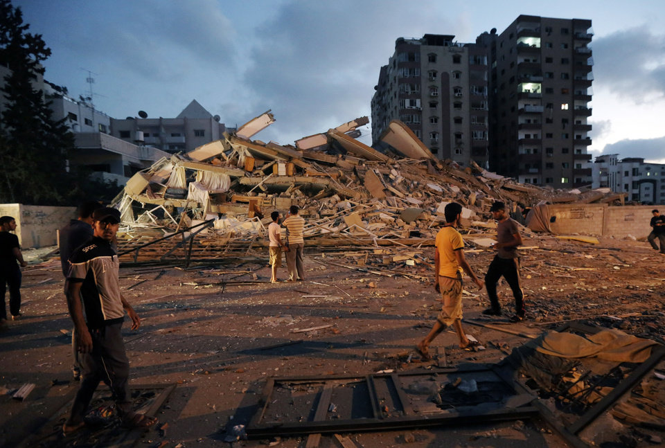Photo - Palestinians inspect the rubble of the al-Zafer apartment tower following an Israeli airstrikes in Gaza City, in the northern Gaza Strip, Saturday, Aug. 23, 2014. Israeli aircraft fired two missiles at a 12-story apartment tower in downtown Gaza City on Saturday, collapsing the building, sending a huge fireball into the sky and wounding at least 22 people, including 11 children, witnesses and Palestinian officials said. (AP Photo/Adel Hana)
