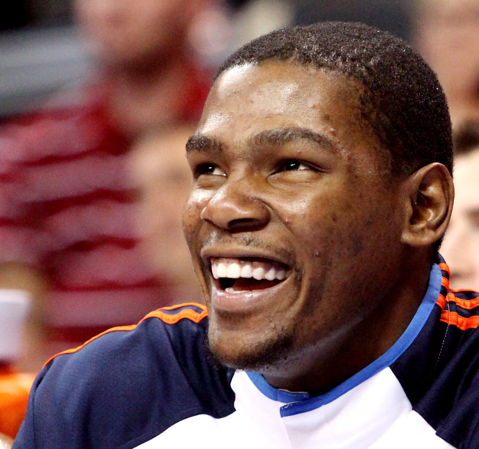 Photo - After being pulled from the game in the fourth quarter, Oklahoma City's Kevin Durant smiles as he watches the Thunder beat Toronto during their NBA basketball game at the Ford Center in Oklahoma City on Sunday, Feb. 28, 2010. The Thunder beat the Raptors 119-99. Photo by John Clanton, The Oklahoman