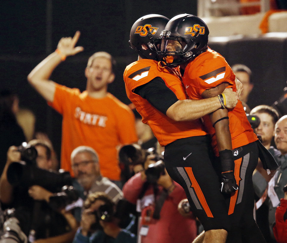 Photo - OSU quarterback J.W. Walsh (4), left, hugs Josh Stewart (5) after Stewart took a Walsh pass for a touchdown in the first quarter during a college football game between Oklahoma State University (OSU) and the University of Texas (UT) at Boone Pickens Stadium in Stillwater, Okla., Saturday, Sept. 29, 2012. Photo by Nate Billings, The Oklahoman
