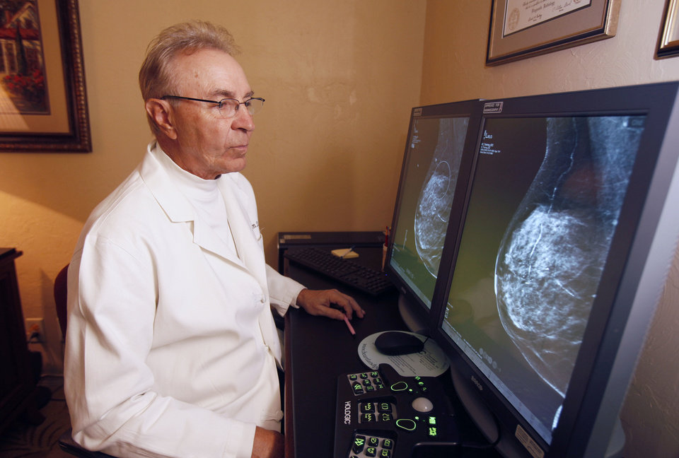Photo - Dr. Larry Killebrew looks at computer images at the Oklahoma Breast Care Center in Oklahoma City on Thursday.  Photo by Paul Hellstern, The Oklahoman  PAUL HELLSTERN