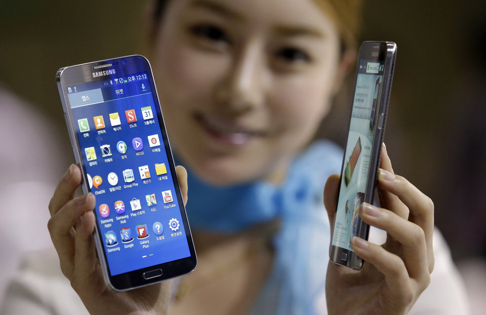 FILE - In this Oct. 10, 2013 file photo, a model poses with Samsung Electronics' smartphones the Galaxy Round at Korea Electronics Show in Goyang, west of Seoul, South Korea. Samsung has released the curved-screened smartphone called the Galaxy Round. It has created some excitement in tech circles but for consumers it does not look much different from the flat screened Galaxy Note 3 phone. The curve in the Round's screen is slight enough to not be apparent without a close look. It is also the most expensive smartphone on sale in South Korea. The Round is an experiment for Samsung with a new phone design.  (AP Photo/Lee Jin-man, File)