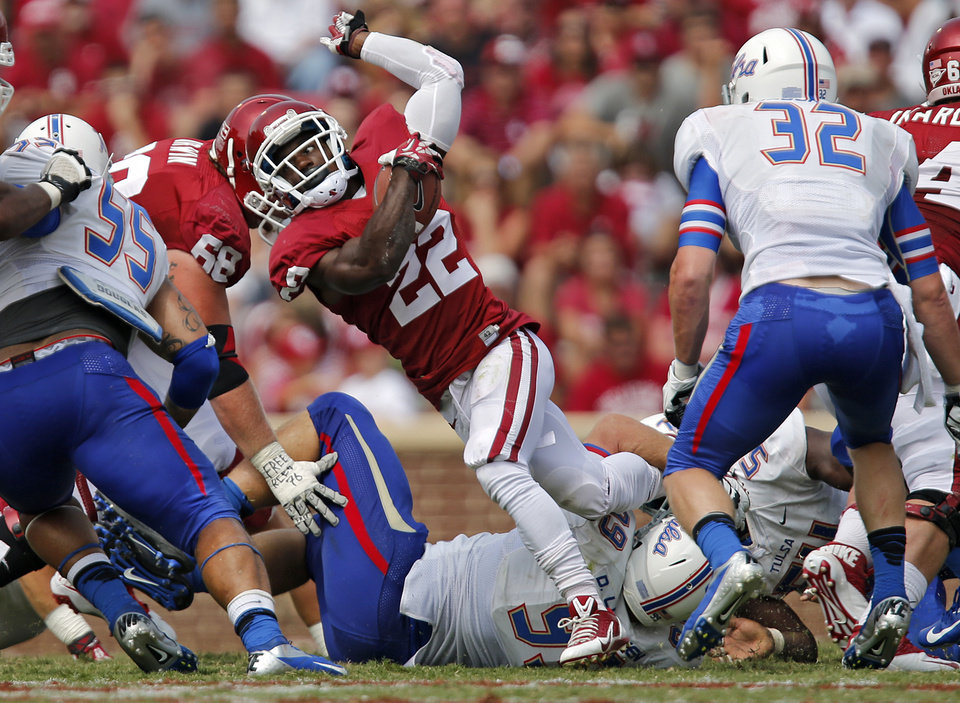 Photo - Oklahoma's Roy Finch (22) twist through the Tulsa defense during the college football game between the University of Oklahoma Sooners (OU) and the University of Tulsa Hurricanes (TU) at the Gaylord-Family Oklahoma Memorial Stadium on Saturday, Sept. 14, 2013 in Norman, Okla.  Photo by Chris Landsberger, The Oklahoman