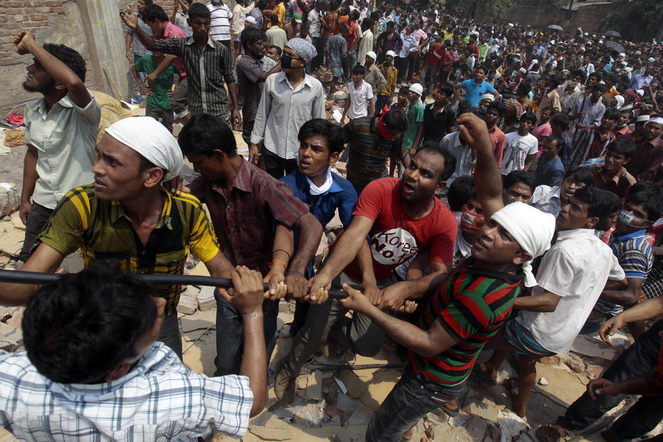 Photo - Bangladeshi rescuers work to pull down rubble at the site of a building that collapsed Wednesday in Savar, near Dhaka, Bangladesh, Friday, April 26, 2013. More than two days after their factory collapsed on them, at least some garment workers were still alive in the corpse-littered debris Friday, pinned beneath tons of mangled metal and concrete. The death toll topped 300 on Friday and it remained unclear what the final grim number would be. (AP Photo/A.M. Ahad)