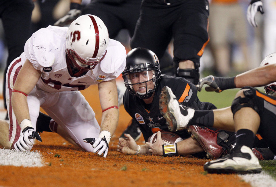 Photo - Oklahoma State quarterback Brandon Weeden, right, looks up for the touchdown signal from the official after rushing for a touchdown in front of Stanford linebacker Terence Murphy, left, during the first half of the Fiesta Bowl NCAA college football game Monday, Jan. 2, 2012, in Glendale, Ariz. (AP Photo/Paul Connors)