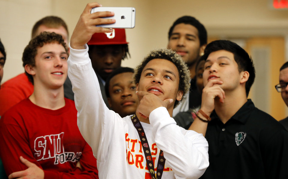 Photo - Cassius Hill takes a group selfie with other athletes who made their college intentions known at Westmoore High School on Wednesday, Feb. 4, 2015  in Moore, Okla. Photo by Steve Sisney, The Oklahoman