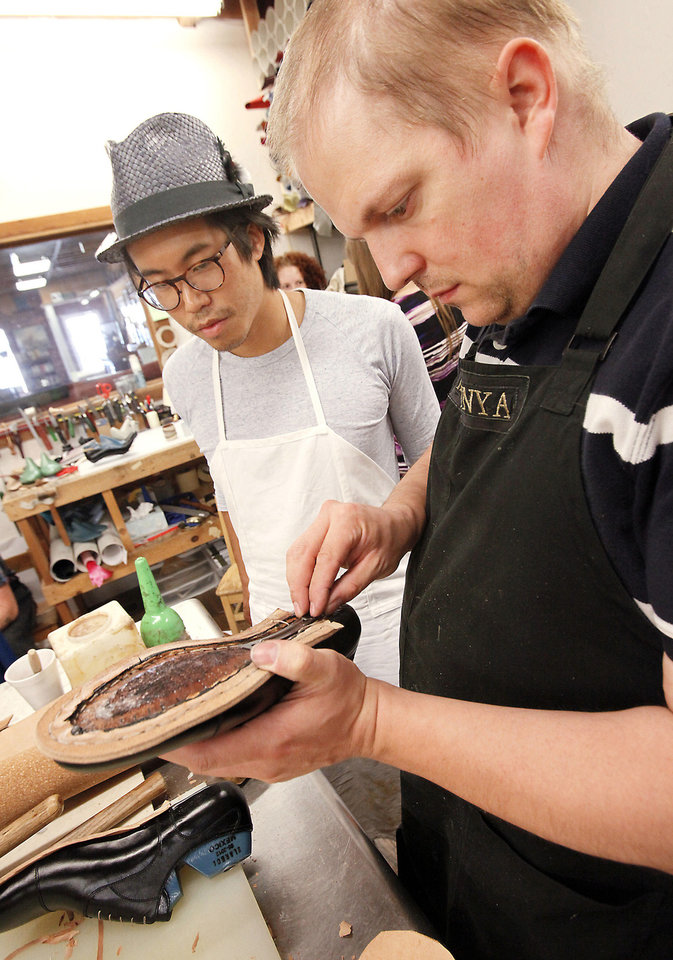 Photo - Hungarian shoemaker Marcell Mrsán, right, works with student Matt Huang, from Toronto on Thursday during a class at Sorrell Custom Boots in Guthrie.  Photo By David McDaniel,  The Oklahoman