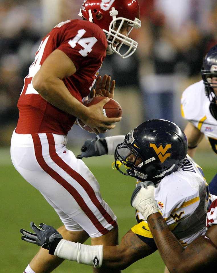 Photo - Sam Bradford (14) is sacked by West Virginia's Johnny Dingle (92) during the first half of the Fiesta Bowl college football game between the University of Oklahoma Sooners (OU) and the West Virginia University Mountaineers (WVU) at The University of Phoenix Stadium on Wednesday, Jan. 2, 2008, in Glendale, Ariz. 