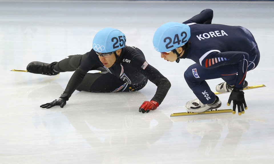 Photo - J.R. Celski of the United States, left, crashes out as he and Park Se-Yeong of South Korea compete in a men's 500m short track speedskating quarterfinal at the Iceberg Skating Palace during the 2014 Winter Olympics, Friday, Feb. 21, 2014, in Sochi, Russia. (AP Photo/Vadim Ghirda)