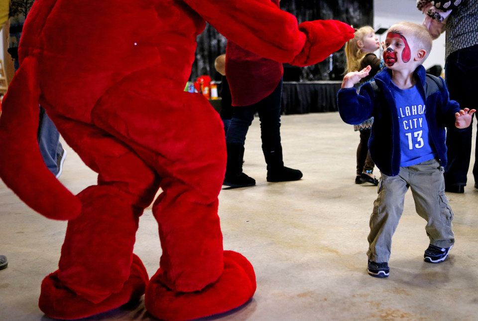 Ashley Lealos, 3, greets Clifford during a birthday party for Clifford the Big Red Dog on Saturday. Photo by Bryan Terry, The Oklahoman <strong>BRYAN TERRY - THE OKLAHOMAN</strong>
