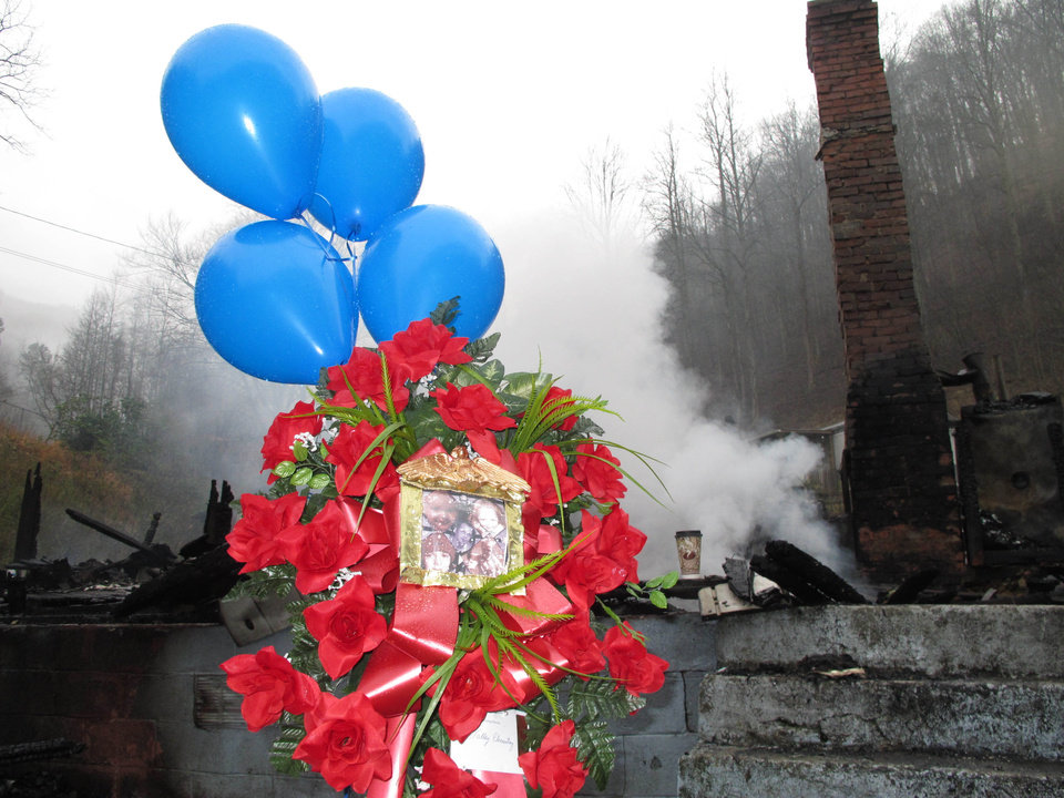 A makeshift memorial stands in front of an eastern Kentucky home that was destroyed in an early morning fire on Wednesday, Jan. 9, 2013, at Jonancy, Ky. Four children and their father were killed in the blaze.(AP Photo/Bruce Schreiner)