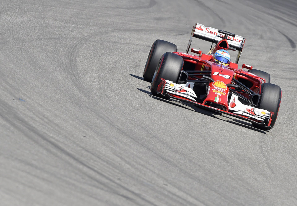 Photo - Ferrari driver Fernando Alonso of Spain speeds during the third free practice session at the German Formula One Grand Prix in Hockenheim, Germany, Saturday, July 19, 2014. The German Grand Prix will be held on Sunday, July 20, 2014. (AP Photo/Jens Meyer)