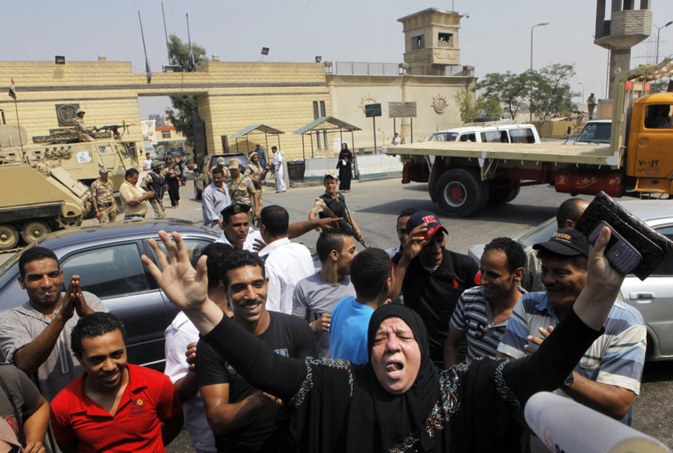 Photo - Supporters of Egypt's deposed autocrat Hosni Mubarak chant slogans in front of Torah prison where he is held, in Cairo, Egypt, Thursday, Aug. 22, 2013. Mubarak is expected to be freed from prison and placed under house arrest on Thursday after being ordered released the previous day, following more than two years in detention. (AP Photo/Amr Nabil)