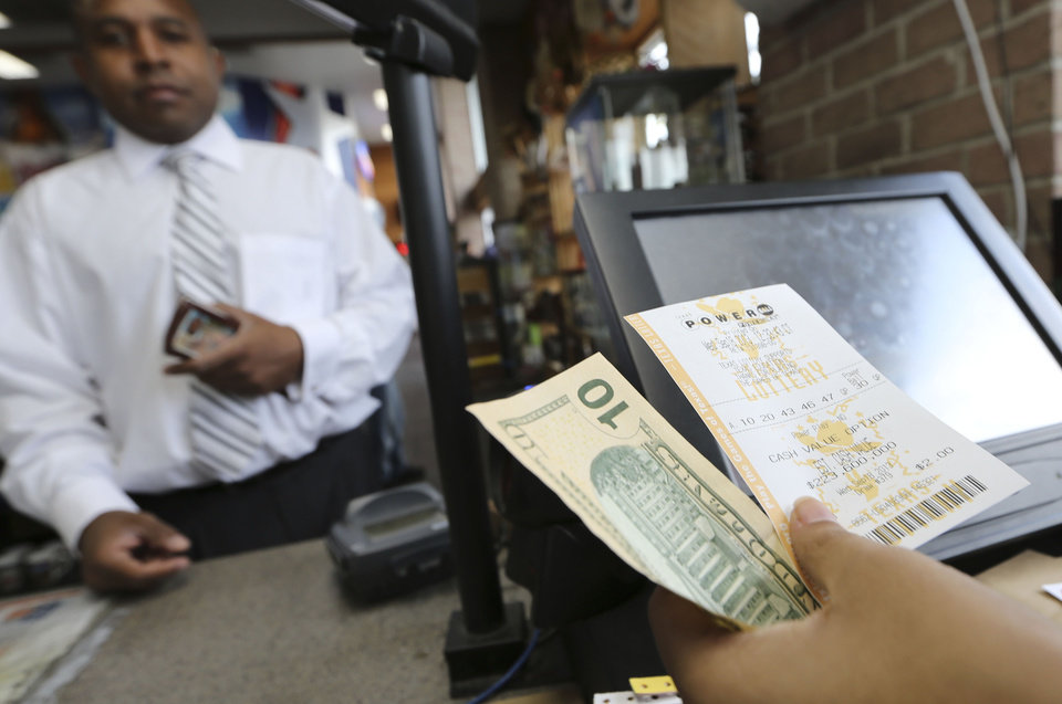 Photo - Larry McKinney, left, waits for his Powerball lottery ticket purchased at the Fuel City store in Dallas on Wednesday, Sept. 18, 2013. For Wednesday's drawing, Powerball's estimated $400 million jackpot will be the nation's fifth-largest ever. (AP Photo/LM Otero)