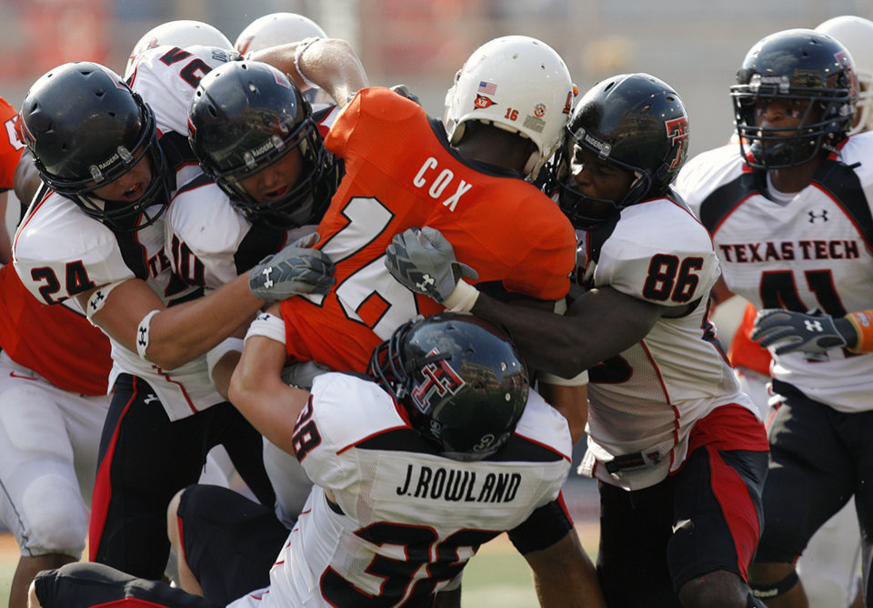 Photo - Oklahoma State's Perrish Cox (16) is stuffed by the Texas Tech defense during the second half of the college football game between the Oklahoma State University Cowboys (OSU) and the Texas Tech University Red Raiders (TTU) at Boone Pickens Stadium in Stilllwater, Okla., on Saturday, Sept. 22, 2007. OSU won, 49-45. By NATE BILLINGS, The Oklahoman