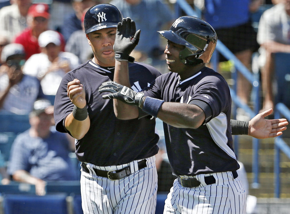 Photo - New York Yankees Carlos Beltran, left, congratulates the Yankees Alfonso Soriano after scoring on Soriano's fourth-inning, two-run home run off Boston Red Sox relief pitcher Brandon Workman in a spring exhibition baseball game in Tampa, Fla., Tuesday, March 18, 2014. (AP Photo/Kathy Willens)