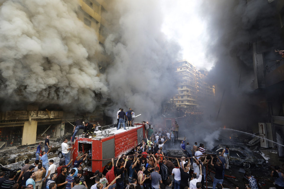 Photo - Lebanese citizens and Hezbollah supporters gather at the scene of a car bomb explosion in southern Beirut, Lebanon, Thursday Aug. 15, 2013. The powerful car bomb ripped through a southern Beirut neighborhood that is a stronghold of the militant group Hezbollah on Thursday, killing at least three people and trapping others in burning buildings, the media said. (AP Photo/Hussein Malla)