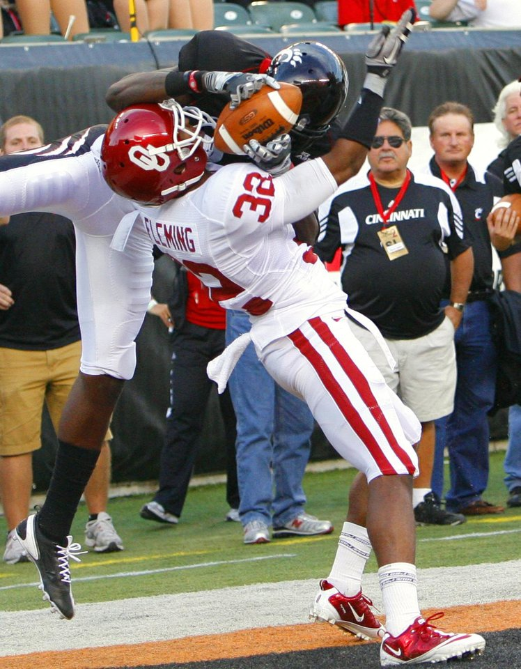Photo - Jamell Fleming (32) strips a pass from receiver Armon Binns (80) in the end zone during the first half of the college football game between the University of Oklahoma Sooners (OU) and the University of Cincinnati Bearcats (UC) at Paul Brown Stadium on Saturday, Sept. 25, 2010, in Cincinnati, Ohio.   Photo by Steve Sisney, The Oklahoman ORG XMIT: KOD