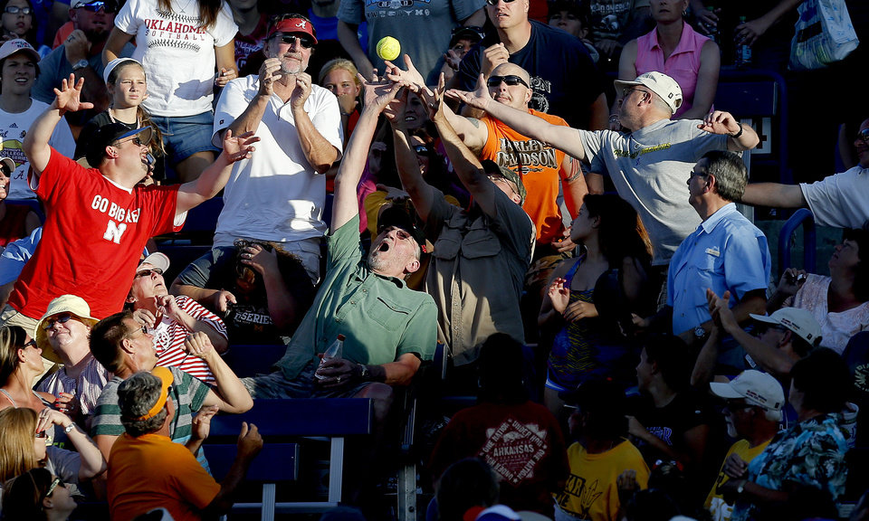 Fans reach for a foul ball during a Women's College World Series softball game between Nebraska and Florida at ASA Hall of Fame Stadium in Oklahoma City, Saturday, June, 1, 2013. Photo by Bryan Terry, The Oklahoman