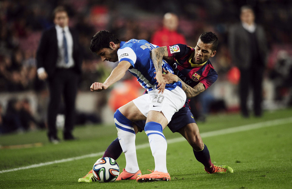 Photo - FC Barcelona's Daniel Alves, from Brazil, right, duels for the ball against Real Sociedad's Jose Angel Valdes during a Copa del Rey soccer match at the Camp Nou stadium in Barcelona, Spain, Wednesday, Feb. 5, 2014. (AP Photo/Manu Fernandez)