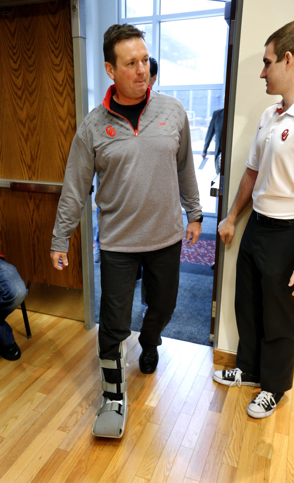 Photo - University of Oklahoma head football coach Bob Stoops is seen wearing a protective boot following toe surgery as he enters a press conference on National Signing Day at OU on Wednesday, Feb. 6, 2013, in Norman, Okla.  Photo by Steve Sisney, The Oklahoman