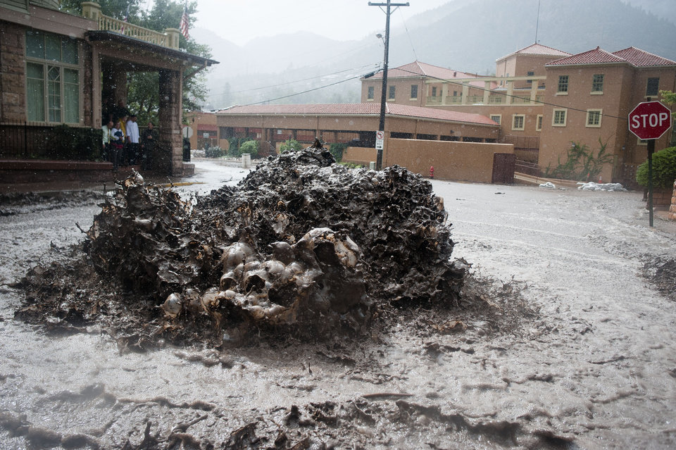 Photo - Flood water shoots out of a sewer on Canon Avenue on Thursday, Sept. 12, 2013, in Manitou Springs, Colo. Flash flooding in Colorado has cut off access to towns, closed the University of Colorado in Boulder and left at least three people dead. (AP Photo/The Colorado Springs Gazette, Michael Ciaglo)