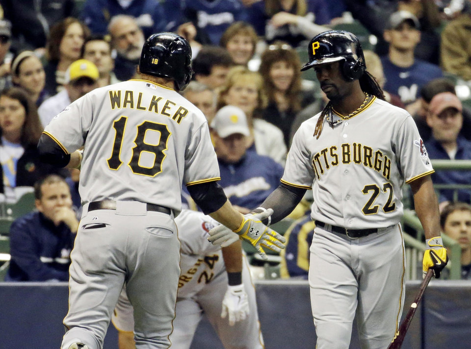 Photo - Pittsburgh Pirates' Neil Walker is congratulated by teammate Andrew McCutchen (22) after Walker hit a home run during the first inning of a baseball game against the Milwaukee Brewers, Tuesday, May 13, 2014, in Milwaukee. (AP Photo/Morry Gash)