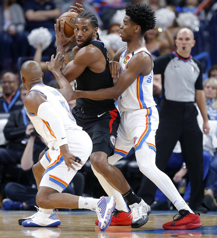 Photo - Oklahoma City's Chris Paul (3) and Shai Gilgeous-Alexander (2) defend LA's Kawhi Leonard (2) during an NBA basketball game between the Oklahoma City Thunder and the Los Angeles Clippers at Chesapeake Energy Arena in Oklahoma City, Tuesday, March 3, 2020. [Bryan Terry/The Oklahoman]