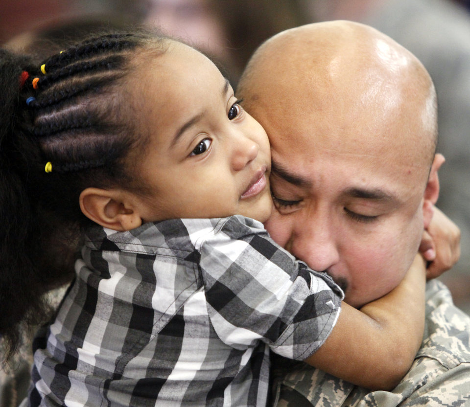 Tech. Sergeant Raul Estrada hugs his 4-year-old daughter Jade during a deployment ceremony for members of the 137th Air Refueling Wing  in Oklahoma City, Oklahoma December 21, 2009.Just before departing the group's flight was canceled due to bad weather on the east coast. Photo by Steve Gooch, The Oklahoman