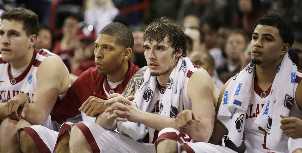 Photo - Oklahoma players on the bench watch in overtime during a second-round game of the NCAA men's college basketball tournament against North Dakota State in Spokane, Wash., Thursday, March 20, 2014. North Dakota State won 80-75 in overtime. (AP Photo/Young Kwak)